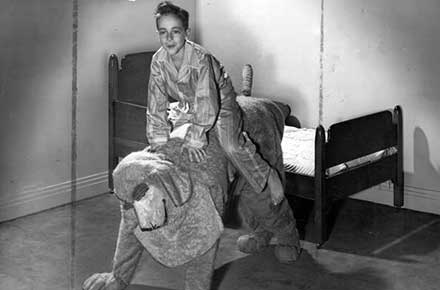 Michael being taken to bed by Nana, the dog nurse, in a scene from Peter Pan, 1942.