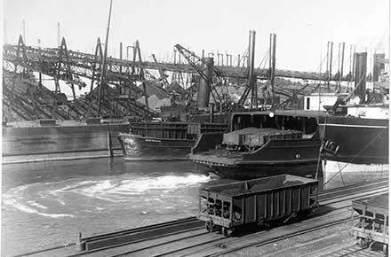 View of harbor with ships, rail cars, and Brownhoists