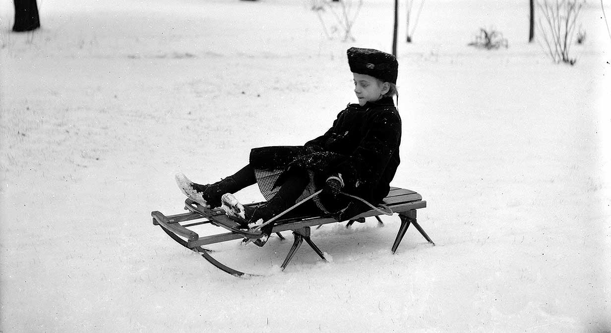 Louise Humphrey sitting on her sled in the yard of her home.