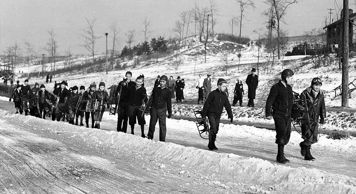 Children heading to the top of the sledding hill in Akron