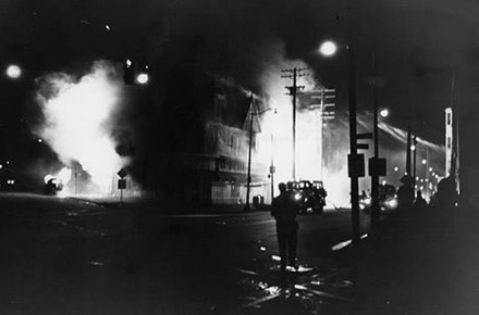 A pharmacy and a supermarket burn in fires set during the Hough riots of 1966