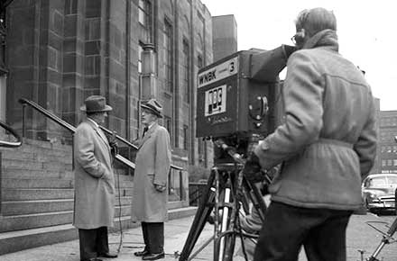 Television reporter prepares a broadcast in front of the courthouse during the Sheppard trial, 1954.