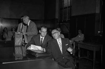Sam Sheppard sits with his lawyers in the courtroom, 1954.