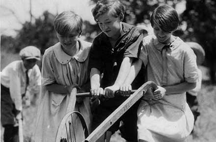 Three Cleveland Public School students work the plow together in the school garden, July, 1927.