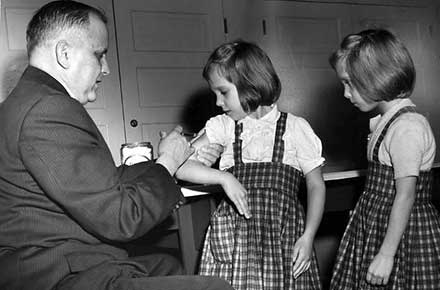 Dr. William Macy gives twin girls injections at the East End Neighborhood House, 1960